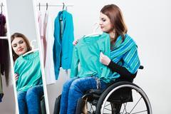 Invalid girl on wheelchair choosing clothes in wardrobe Stock Photos