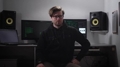 Portrait of a hacker sitting on the chair with computer monitors and Stock Footage
