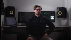 Serious hacker looking directly the shot, he is dressed in a dark jacket Stock Footage