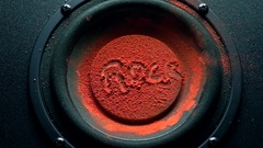 Rock inscription on orange powder over trembling loudspeaker. Super slow motion Stock Footage