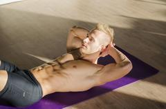 Handsome young man doing abs exercises on mat Stock Photos