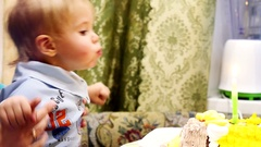 Little happy boy blows out the candle on the cake sits with mum celebrating Stock Footage
