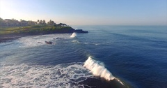 Rocky coast and traditional oriental buildings on the cliff. Waves and ocean Stock Footage