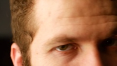 Close the eyes of a young white man with curly hair plan. The man turns his head Stock Footage