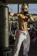 Shirtless young man using punching bag Stock Photos