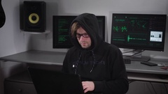 Hacker offender carries out clandestine cyber attacks with the use of a laptop Stock Footage