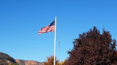 Usa flag waving in front of the blue sky and the town of Kanab, in Utah, Un.. Stock Footage