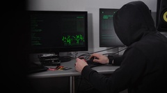 Back view of a hooded hacker making cyber attack on bank network. Man in black Stock Footage
