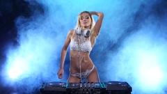 DJ woman in the smoke plays two songs. Smoky studio Stock Footage