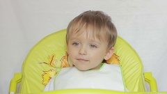 Baby boy sitting on a table laughing child eyebrows moves. Stock Footage