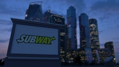 Street signage board with Subway logo in the evening.  Blurred business distric Stock Footage