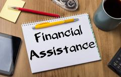 Financial Assistance - Note Pad With Text On Wooden Table Stock Photos