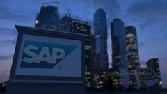 Street signage board with SAP SE logo in the evening.  Blurred business distric Stock Footage