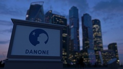 Street signage board with Danone logo in the evening.  Blurred business distric Stock Footage