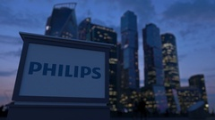 Street signage board with Philips logo in the evening.  Blurred business distric Stock Footage