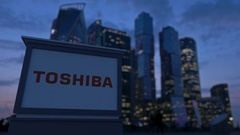 Street signage board with Toshiba Corporation logo in the evening.  Blurre Stock Footage