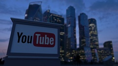 Street signage board with YouTube logo in the evening.  Blurred business distric Stock Footage