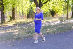 Pretty Blond Expectant Mother Walking on Sunny Day in Park, Stop Kuvituskuvat