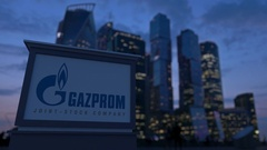Street signage board with Gazprom logo in the evening.  Blurred business distric Stock Footage