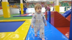 The One Year Old Cute  is Making His First Steps In Indoors Playground. Act.. Stock Footage