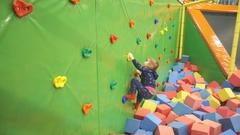 Little Girl Climbing a Rock Wall Indoor. Children's Entertainment Sports So.. Stock Footage