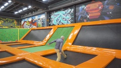 Young Men Jumping At Trampoline In Indoors Playground. Active People Male Stock Footage