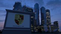 Street signage board with Porsche logo in the evening.  Blurred business distric Stock Footage