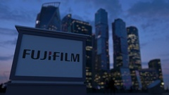 Street signage board with Fujifilm logo in the evening.  Blurred busines Stock Footage