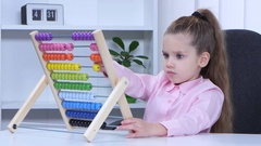 Little girl in shirt sitting at the table and said to the multicolored aba Stock Footage