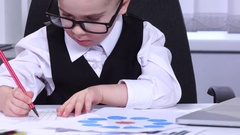 Little boy businessman looking at charts and data are entered into a laptop Stock Footage