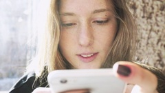 Girl Caucasian smiling texting on the phone. Smile  during rewriting on phone Stock Footage
