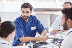 Thrilled doctor arguing with associates during meeting Stock Photos