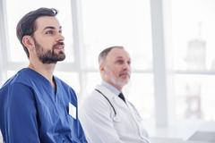Smiling physicians looking report in hospital room Stock Photos