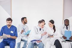 Outgoing physicians arranging lectures in clinic Stock Photos