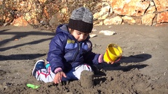 Child plays in wet sand on cool sunny day Stock Footage