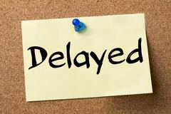 Delayed - adhesive label pinned on bulletin board Stock Photos