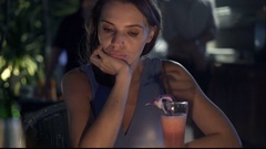 Sad, pensive woman sitting in cafe during night Stock Footage