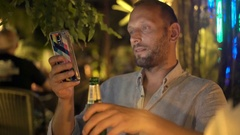 Young man using smartphone and drinking beer in cafe in the garden at night, 4K Stock Footage