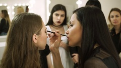 Professional female make-up artist teaching visagistes to the art of make-up. HD Stock Footage