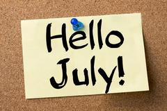 Hello July! - adhesive label pinned on bulletin board Stock Photos