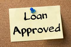 Loan Approved - adhesive label pinned on bulletin board Stock Photos