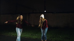 Girls in trendy clothes dancing on city street sidewalk in spot light night Stock Footage