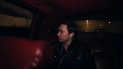 Young guy on leather car backseat with headphones riding on night city streets Stock Footage