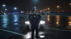Young man in leather jacket stand in front of car on night shopping mall parking Stock Footage
