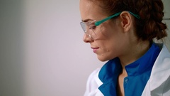 Woman scientist in safety glasses. Close up of female scientist face Stock Footage