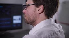 The man with glasses and a white shirt very quickly typing on the computer Stock Footage