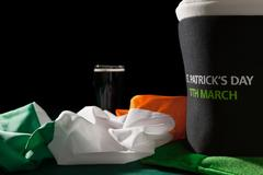 St Patrick day with a pint of black beer, hat and irish flag over a green table Stock Photos