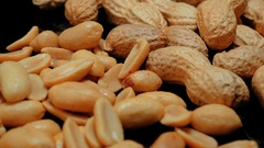 Camera slides over roasted peanuts in a close up or macro shot Stock Footage