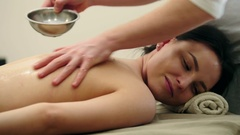 Man rubs sesame oil - massage for young female Stock Footage