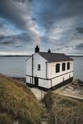 Landscape image of derelict abandoned fishing house on England Solent coast.. Stock Photos